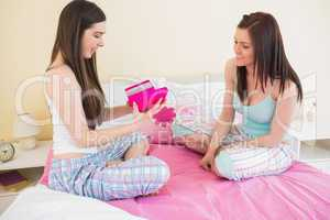 Happy girl in pajamas opening a present from her friend