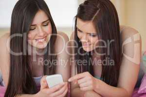 Happy friends in pajamas looking at smartphone on bed