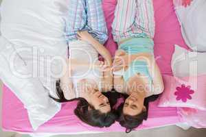 Pretty friends in pajamas looking at smartphone on bed