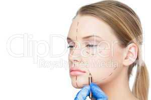 Surgeon drawing dotted lines on pretty patient