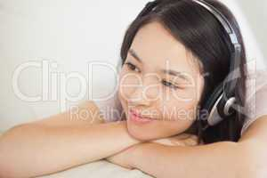 Relaxing asian girl lying on the sofa and listening to music