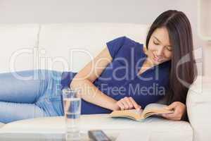 Happy asian girl lying on the sofa reading a novel