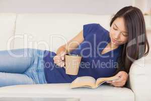 Beautiful asian girl lying on the sofa reading a novel and drink