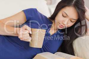 Attractive asian girl lying on the sofa reading a novel and drin