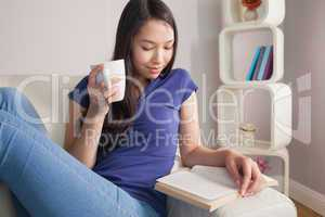 Reading young asian woman sitting on the couch holding mug