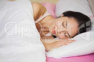 Peaceful young asian woman sleeping in her bed