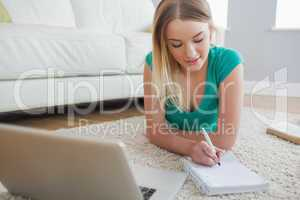 Smiling blonde lying on floor doing her assignment using laptop