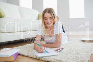 Smiling blonde woman lying on floor sketching on paper