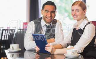 Business team working on tablet pc together in a cafe