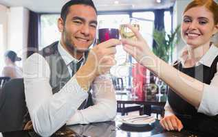 Smiling business partners clinking wine glasses looking at camer
