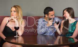 Blonde woman feeling alone as two people are flirting beside her