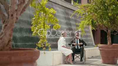 11of15 Health and handicap, business people on wheelchair outdoors