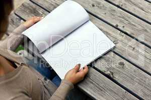 Young woman sitting at the table with a booklet