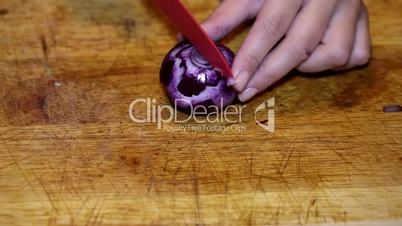 Cutting purple onion on wooden plate closeup