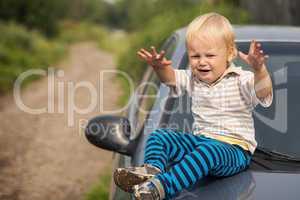 boy cries by the car
