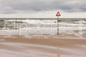 warnschild an der nordsee, danger label at the north sea
