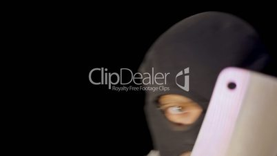 Masked criminal showing chopper knife close up
