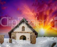 Chapel surrounded by snow on a mountan peak. Beautiful sunset co