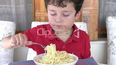 Young boy eating spaghetti
