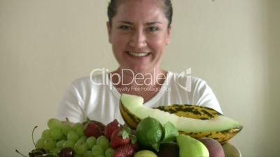 Woman showing  lots of fruits in the  dish