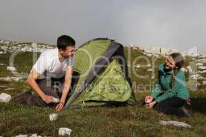 junge leute bauen ein zelt auf in den bergen