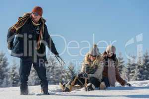young people enjoy sunny winter day sledge