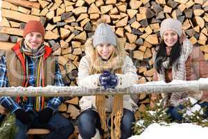 young people sitting outside winter clothes wood