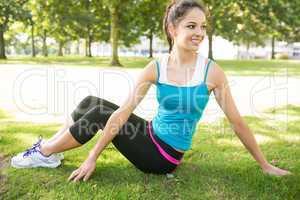 Active smiling brunette stretching her back