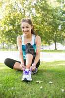 Active cheerful brunette tying her shoelaces