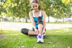 Active content brunette tying her shoelaces