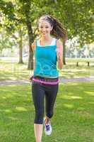 Active smiling brunette jogging