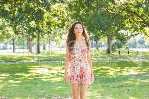 Stylish day dreaming brunette walking on grass