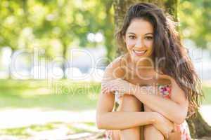 Stylish cheerful brunette sitting under a tree