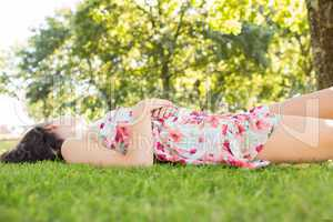Stylish peaceful brunette lying on a lawn