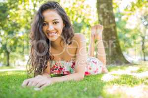 Stylish smiling brunette lying on a lawn looking at camera