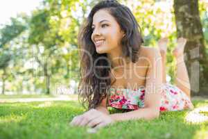 Stylish cheerful brunette lying on a lawn looking away