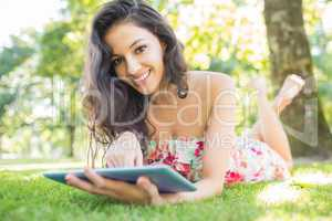 Stylish smiling brunette lying on a lawn using tablet