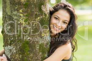 Casual smiling brunette embracing a tree looking at camera