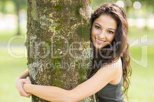Casual cheerful brunette embracing a tree looking at camera