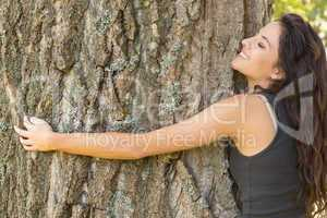 Casual content brunette embracing a tree with closed eyes