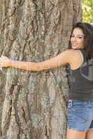 Casual attractive brunette embracing a tree looking at camera