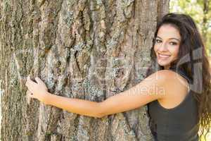 Casual beautiful brunette embracing a tree looking at camera