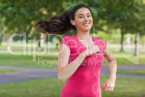 Motivated pretty woman jogging in a park