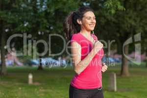 Motivated sporty woman running in a park
