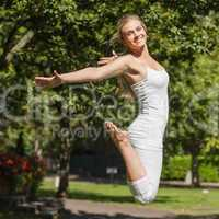 Side view of young fit woman jumping spreading her arms