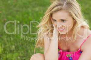 Content cute woman sitting on a lawn