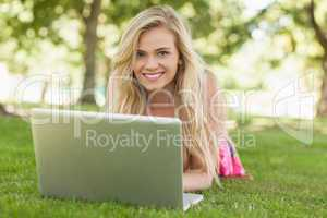 Peaceful attractive woman using her notebook lying on a lawn