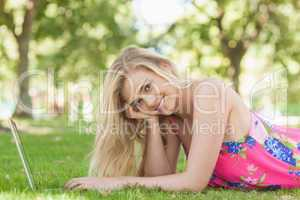 Portrait of gorgeous woman using her notebook lying on a lawn