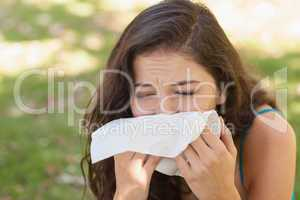 Sick young woman using a handkerchief