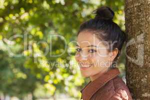 Beautiful young woman posing leaning against a tree